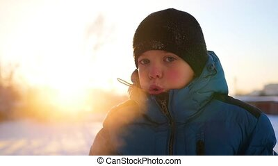 child blowing steam from his mouth on a cold day