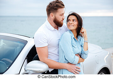 Young beautiful couple in love standing at car