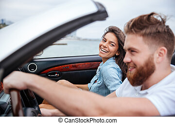 Joyful couple smiling while riding in their convertible car