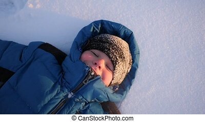 the child is lying on snow and smiling. Winter time.