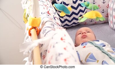 Little baby lying in his bed, looking at toys - The small...