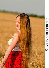 Girl with long hair in a wheat field, standing in a...