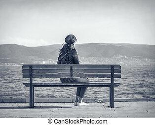 Girl on the bench near the sea. - Woman sitting on the bench...