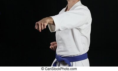 The fighter in white kimono with a blue belt making punch