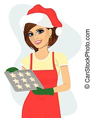 young beautiful woman in santa hat holding tray with baking cookies