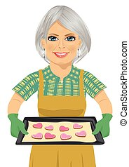 senior woman holding baking tray with heart shape cookies