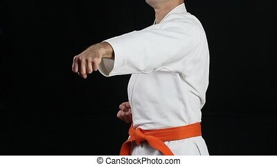 The athlete in a white kimono with an orange belt making punch