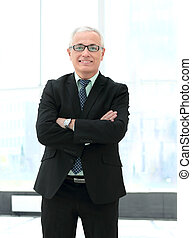 Portrait of confident and smiling businessman looking at the...