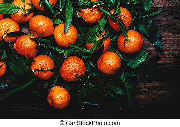 Tangerines with leaves on wooden background. Mandarins...