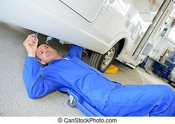 Mechanic on trolley under camper van