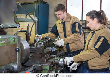 employees using industrial machinery at factory