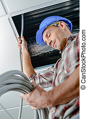 Electrician working in a ceiling hatch