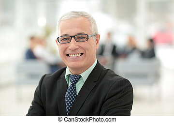 Mature friendly white-haired businessman in a modern office...