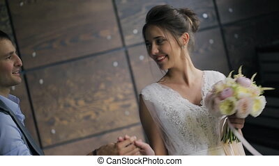 Bride and groom holding hands on photo shoot inside