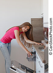 Beautiful young woman made up the dishes in the dishwasher....