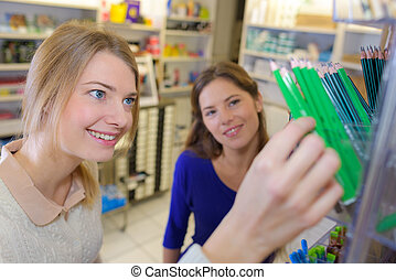 cheerful young girl and friend choosing pencils at a...
