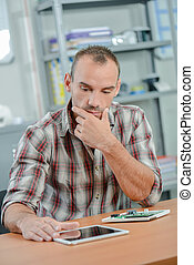 Man looking at tablet, troubled expression