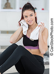 woman resting on mat while towell drying her sweat