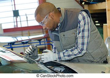 mechanic using repairing equipment to fix damaged windshield