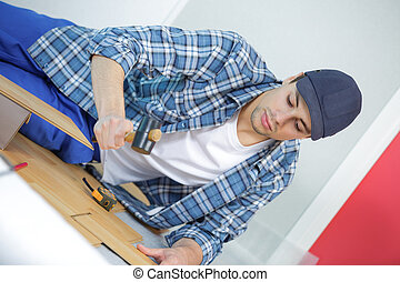 repair building and home concept - male measuring wood flooring