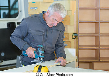mature man cutting wood with saw blade