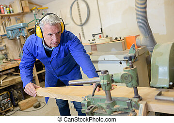 mature carpenter working at a workshop