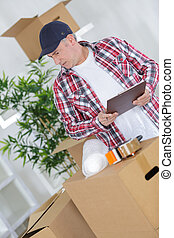middle age man packing cardboard box with sellotape