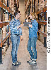 Man and lady holding tablet computer in warehouse