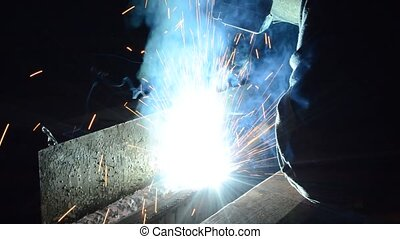A industrial welder - Welder uses torch to make sparks...