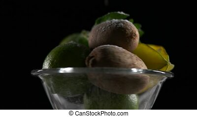 tropical fruits revolve on a surface black background.