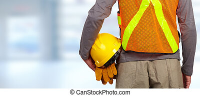 Worker with helmet in orange security vest. - Construction...
