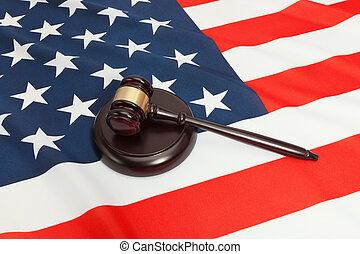 Studio shot of a judge gavel and a soundboard over USA flag...