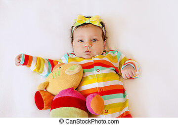 Face of cute surprised baby infant girl in colored pajamas with a bow on her head, making funny mouth expression.