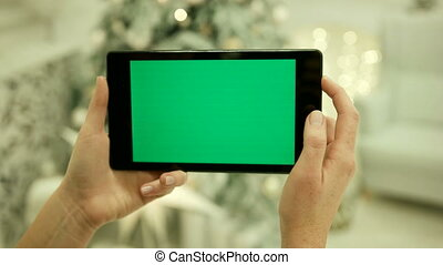 Close-up of female hands touching green screen on tablet Green screen Chroma Key. Close up. Tracking motion. Vertical.with blur christmas decoration background