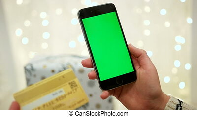 Hands holding credit card and using mobile smart phone...