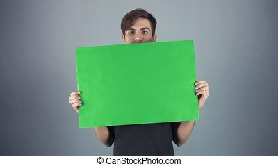 Happy Young man in black shirt holding green key sheet...