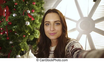 Young smiling woman sitting close to Christmas tree and...
