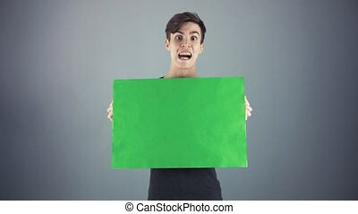 Scared Young man in black shirt holding green key sheet poster gray background