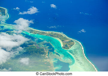 Aerial view of the island with clouds, reef and lagoon. Island near Tahiti in the tropical archipelago of French Polynesia inside the Pacific ocean.