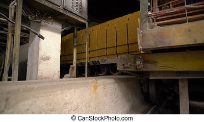 Brick Industry. View of loaded carts ride on rails, close-up
