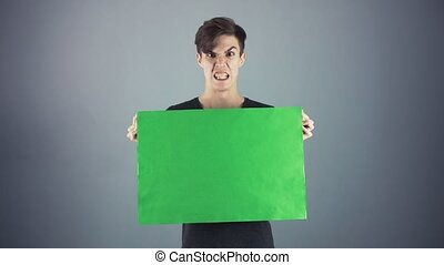 Angry Young man in black shirt holding green key sheet...