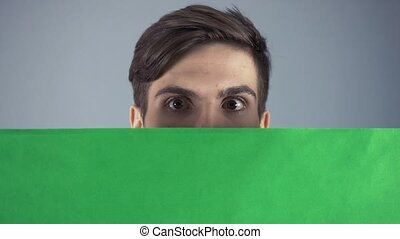 Curious Young man in black shirt holding green key sheet...