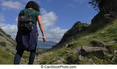 Woman hiking in Lake District - Woman climbing up the stone...