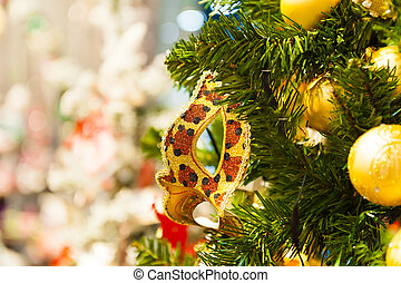 Beautiful carnival mask hanging on the Christmas tree in the background of bright Christmass decorations