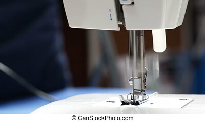 Sewing machine on the table closeup. Machine needle moves. -...