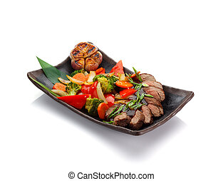 Roasted veal with vegetables on a black plate isolated on...
