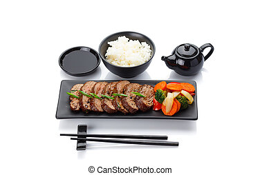 Roasted veal with vegetables on a black plate with rice soy...