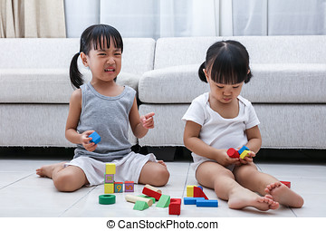 Asian Chinese little sisters struggle for blocks on the...