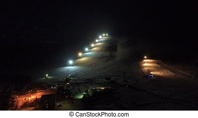 Night flight to the slope of the ski resort. Light from the...