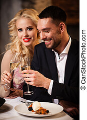 Couple celebrating in restaurant - Happy couple tasting...